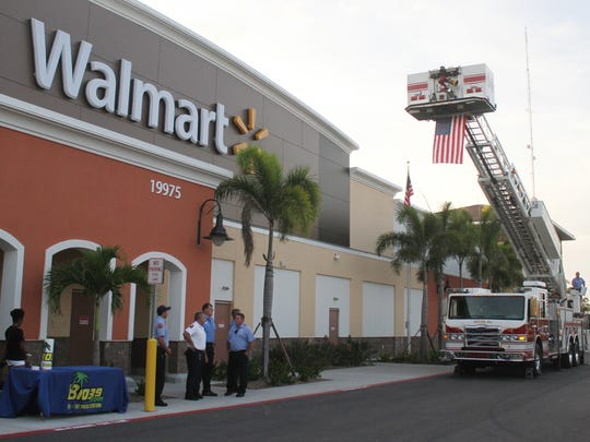 Members of the San Carlos Park Fire and Rescue hoist an American flag up on a ladder truck in preparation for the grand opening of the new Village of Estero Wal-Mart on Wednesday.