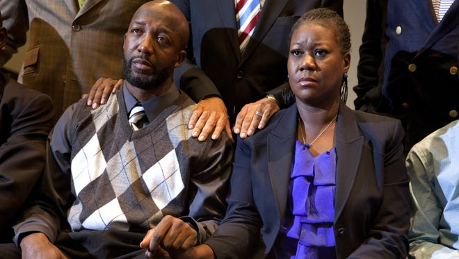 The parents of Trayvon Martin, Sybrina Fulton, right, and Tracy Martin, left, watch a news conference on April 11, 2012, in Washington, D.C., as special prosecutor Angela Corey in Sanford, Fla., announces charges against George Zimmerman.