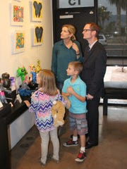 Miles O'Neal, 8, center, looks for his art worth with his sister, Sophia, 6, mom, Sara, and dad, Patrick.