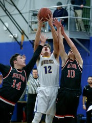 Irondequoit's Tanner Pioch reaches for the ball between Hilton's Mitchell Carr and Mitchell Carr in the first quarter at Irondequoit High School.