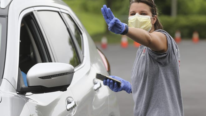 Members of the Tuscaloosa COVID-19 incident command team pass out masks during a drive-thru distribution at the Tuscaloosa Amphitheater Tuesday, July 7, 2020. Tara Newman signals how many masks are needed as a driver moves forward to pick them up.