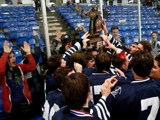 Cranbrook-Kingswood's players celebrities with the championship trophy in front of their fans after their 4-0 win over Houghton in MHSAA Division 3 hockey championship at Compuware on Saturday, March 14, 2015 in Plymouth.