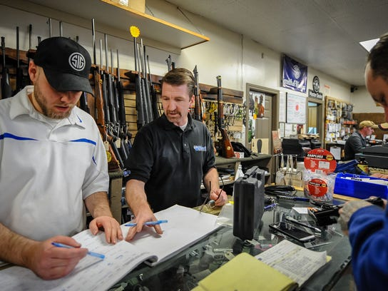 Chaz Smith, left, Dave Larsen, owner of Doug's Shoot'n Sports, and gunsmith Dustin Hamann, of Hamann Engineering, log-in firearms that need to be repaired at Doug's Shoot'n Sports in Taylorsville on Tuesday, April 17, 2018.