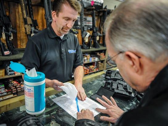 Dave Larsen, left, has Robert Miska, MD, put a fingerprint on his handgun paperwork at Doug's Shoot'n Sports in Taylorsville on Tuesday, April 17, 2018.