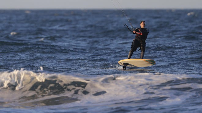 A windsurfer races along the shoreline at New Brighton Beach in Christchurch, New Zealand, Tuesday, June 9, 2020. New Zealanders enjoyed their first day at alert level 1 after Prime Minister Jacinda Ardern announced Monday, June 8 that the Cabinet had agreed to remove almost all remaining coronavirus restrictions from midnight, with the exception of the border strictures.