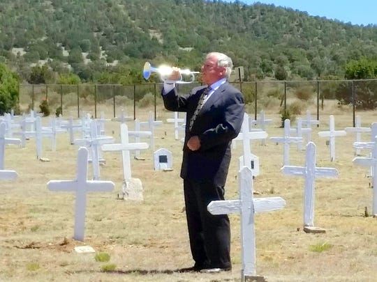 Taps was trumpeted while more than 50 volunteers placed flags on the graves in Fort Stanton Cemetery for Memorial Day. They came from all over, inclduing a honeymooning couple from Texas, several young families and even a few dogs. The Legion Riders rode up from Alamogordo.