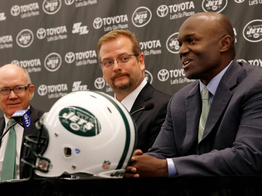 New York Jets owner Woody Johnson, left, and new general manager Mike Maccagnan, center, listen as new head coach Todd Bowles speaks during an NFL football press conference introducing the team's new management, Wednesday, Jan. 21, 2015, in Florham Park, N.J. (AP Photo/Julio Cortez)