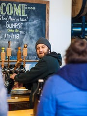 Mark Babson fills a growler for customers at River