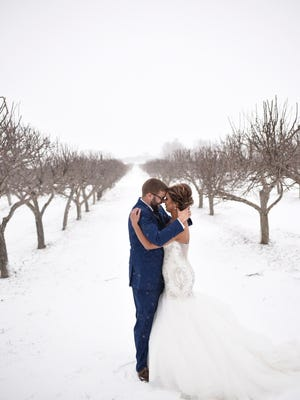 Cody Linneweber, 27, and M'Lynn Linneweber, 28, pose for a picture on their wedding day, Saturday. The two braved record snowfall to get married in Harrisburg.