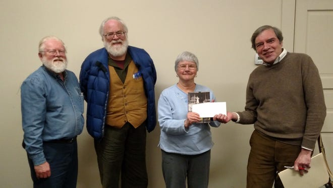 Linda Barth presents a check to John Fedors, president of the Wallace House and Old Dutch Parsonage Association. Looking on are co-authors Robert H. Barth and James L. Sommerville III.