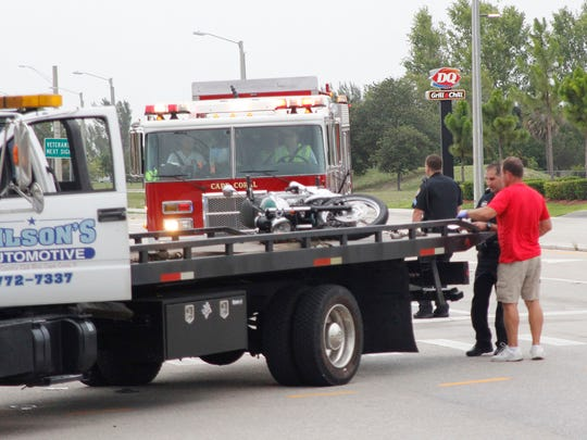 A tow truck takes away the motorcycle of the first