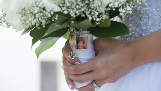 This July 5, 2015 photo provided by Lauren Chertok shows Chertok holding her bouquet on her wedding day. A photo of Chertok's late Aunt Rosie Van Acker is pinned to her bouquet. (Barattini Productions/Lauren Chertok via AP)