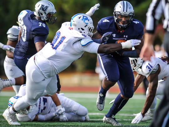 Monmouth University running back Devell Jones battles for yards against Presbyterian's Imani Heslop during Saturday's game in West Long Branch on Nov. 4, 2017.