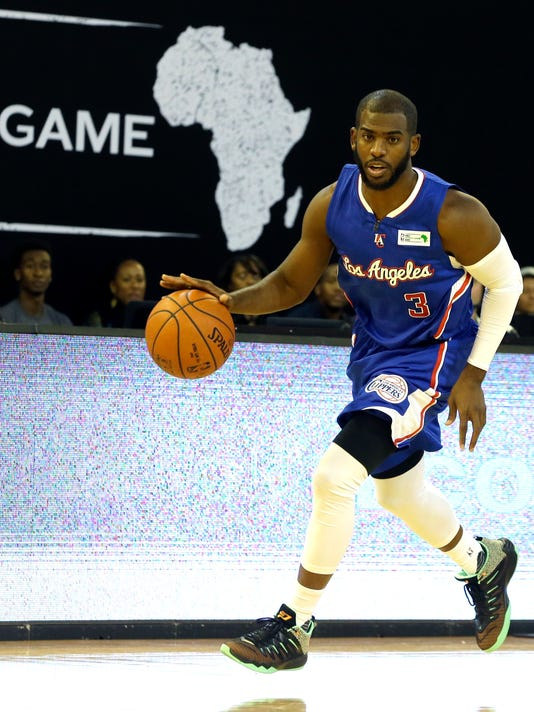 FILE - In this Aug. 1, 2015 file photo, Team World's Chris Paul of Los Angeles Clippers drives the ball against Team Africa during the NBA Africa Game at Ellis Park Arena in Johannesburg, South Africa, Saturday, Aug. 1, 2015. The NBA is making a new play for fans in Africa by splitting with the continent's biggest sports broadcaster and teaming up with a Zimbabwean telecommunications entrepreneur who started his first business with $75.  (AP Photo/Themba Hadebe, File)