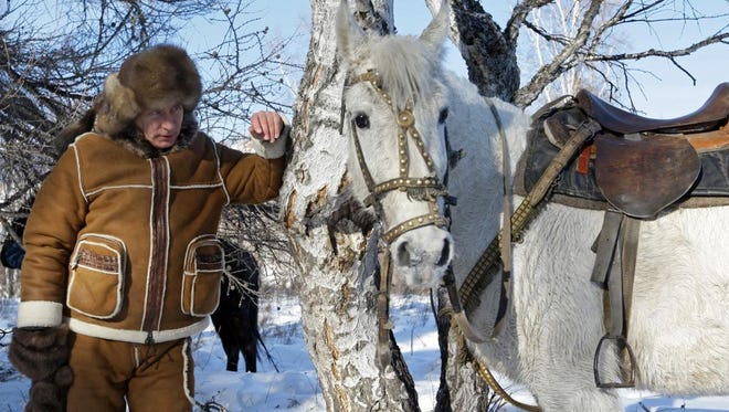 Vladimir Putin stands next to a horse during a working visit to the Siberian Khakasiya region in 2010. This photo is the featured image for February 2016 in the new fan calendar made in the Russian president's honor.