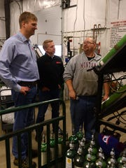 Glenn Bliss, left, president of General Distributing and Monte Ruud, center, CFO of General Distributing, talk to Trevor Dahley in the cylinder filling plant in Great Falls.