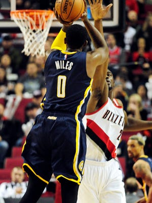 Indiana Pacers forward C.J. Miles (0) hits a three point shot over Portland Trail Blazers forward Noah Vonleh (21) during the first quarter of the game at Moda Center at the Rose Quarter.