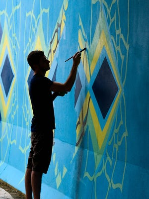 """MIKE LAWRENCE / COURIER & PRESSGraphic designer Jon Whitman paints on a mural he designed under the I-69 and U.S. 41 overpass recently. Whitman said """"I wanted something that felt modern, vibrant and wouldn't look dated in 10 years. It had to be timeless,"""" July 28, 2016."""