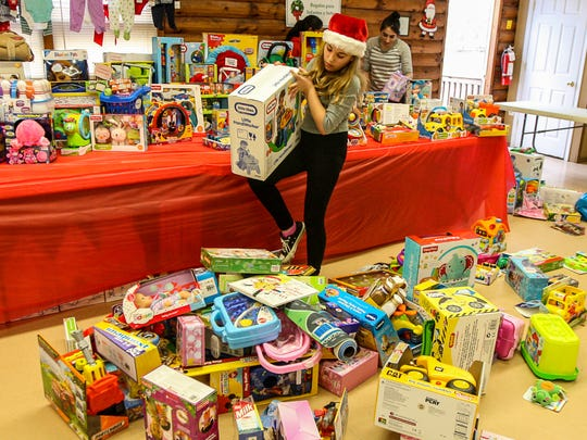 Kelly Rich, 12, of Monroe works with a gift as Middlesex County 4H teens and preteens set up their gifts in the 4H cabin at Middlesex County Fairgrounds in East Brunswick on Saturday December 12, 2015 for their annual Project Gift event on Sunday.