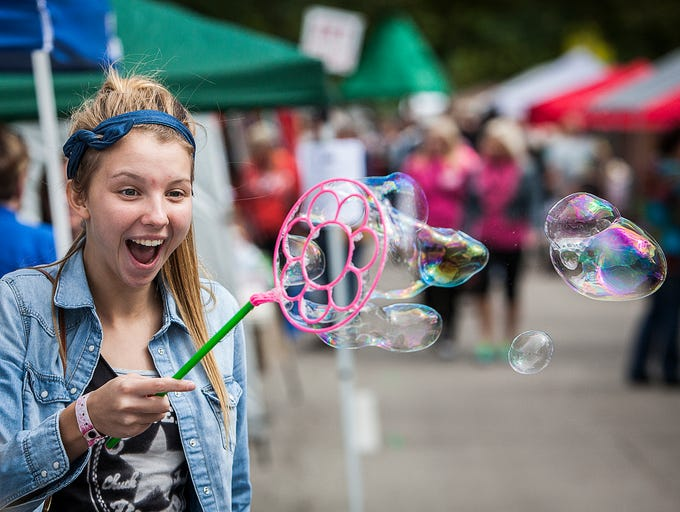 Reagan Martin takes advantage of a free bubble wand setup during the Old Washington Street Festival Saturday.  The event, which was started in 1977, continues Sunday on East Washington Street from 11 a.m. to 5 p.m.