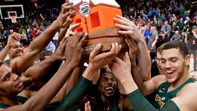 Michigan State players hoist the PK80 trophy after Sunday's 63-45 blowout of North Carolina in Portland, Ore.