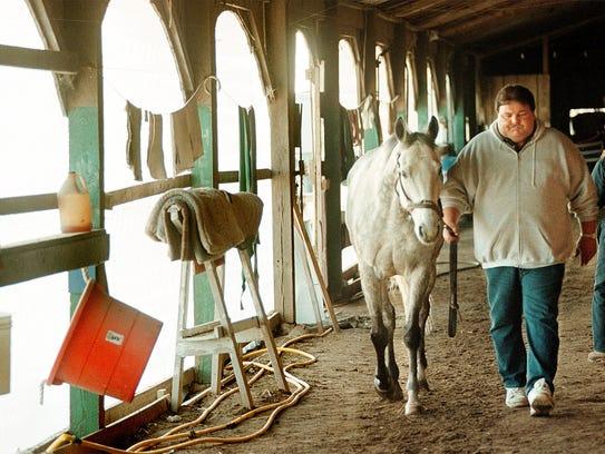 Horse trainer John Hancock walks his horse Ceasar's