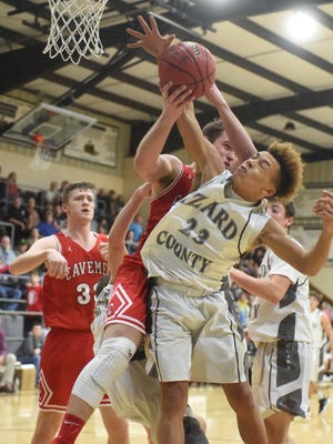 Izard County's Rory Bell battles Cave City's Curt Jones for a rebound on Saturday night in the Izard County Invitational championship game.