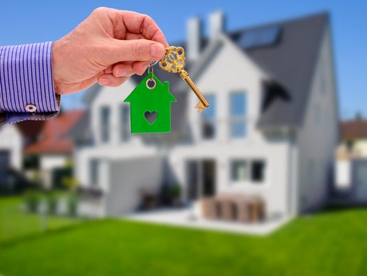 house key on ring in hand of real estate agent