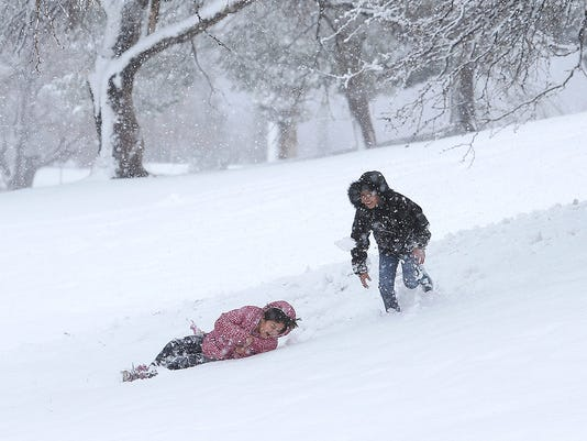 Kids play in the snow at Memorial Park.
