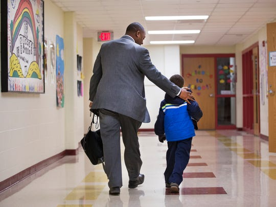 Principal Ceair Baggett walks Rayshawn Allen down the hall for some him quiet time. Sometimes, students need some  extra attention.