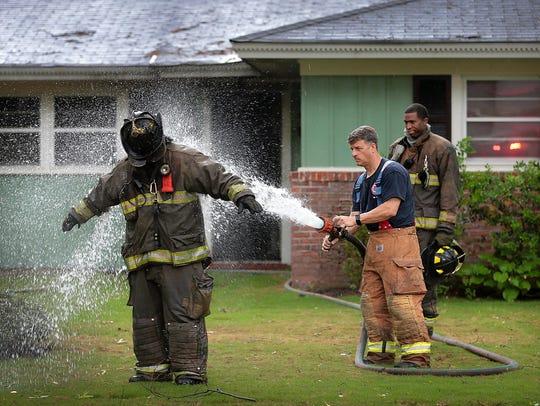 Memphis firefighter Jeremy Chastain (left) is hosed