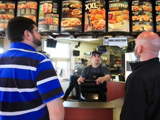 Rick Catapano, center, takes an order from Blake Payne,