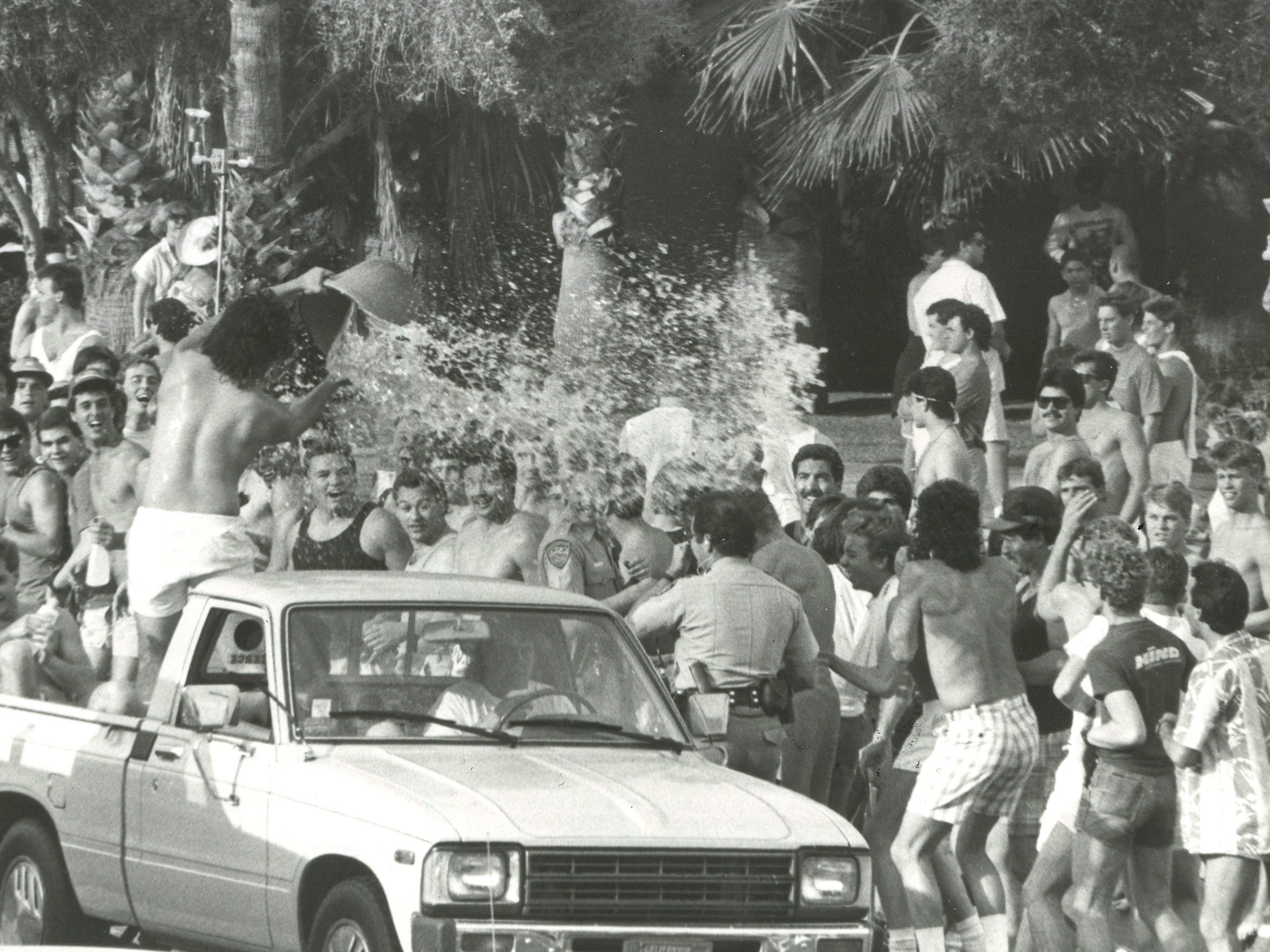 A spring breaker dumps water on police officers in Palm Springs in 1986.