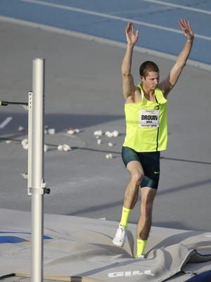Derek Drouin reacts to the crowd after clearing the bar in the high jump at Drake Relays. April 25, 2014, Des Moines, Iowa. (AP Photo/Charlie Neibergall)