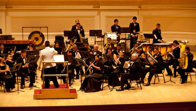 In this 2012 photo, Maximo Ronquillo Jr., musical director and chief band master of the Guam Territorial Band, leads the band in the New York Band and Orchestra Festival at Carnegie Hall in New York City.