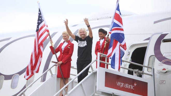 Sir Richard Branson, center celebrates his arrival to Detroit Metro Airport on his airline, Virgin Atlantic, via its new route between London Heathrow and Detroit  on Thursday, June 11, 2015.