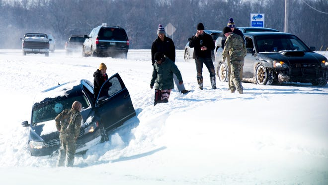 People try to dig a car out of a ditch on Gate 7 Road on January 16, 2018.