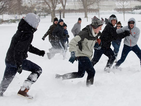 A view of people playing football on the grounds at the U.S. Capitol during a blizzard.