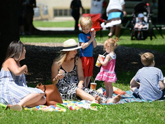 Families eat a picnic lunch Thursday in Whitney Park as the music group Patchouli plays during the Summer in the Park Music Series.