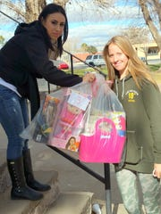 Minister Lucy Montes, left,  hands out a bag of toys