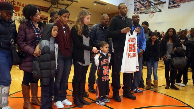 The family of Markus Austin, the former White Plains High School basketball star killed in Vermont over the weekend, was honored before Thursday's game against Mount Vernon at White Plains High School. Head basketball coach Spencer Mayfield presented jerseys with Austin's number to Austin's son, Marquis, 4, and brother Devon. With Marquis is Austin's girlfriend, Caryn Pletzer.