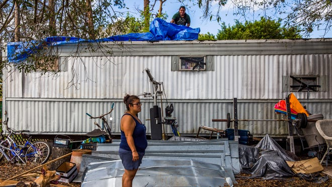 Samantha Tindell stands outside her damaged Immokalee trailer as her partner Antonio Martin puts a tarp over the roof Saturday, Sept. 23, 2017. Tindell and her partner and two children had been sleeping in a tent due to damage and mold in their home, until a thunderstorm flooded their tent after this photo was taken.