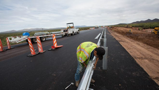 Manuel Mendoza, along with a work crew from San Bar Construction of Albuquerque, installs guard rails along the newly paved southern road to Spaceport America on Thursday, July 12, 2018. After years of delays the southern road to Spaceport America is finally reaching completion. The road has been paved but is awaiting road signage, striping and the completion of guard rails in some sections.