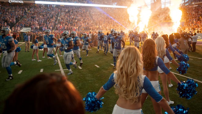The Detroit Lions take the field as the Lions cheerleaders dance before the home opener against the Tennessee Titans on Sunday, Sept. 18, 2016 at Ford Field in Detroit.