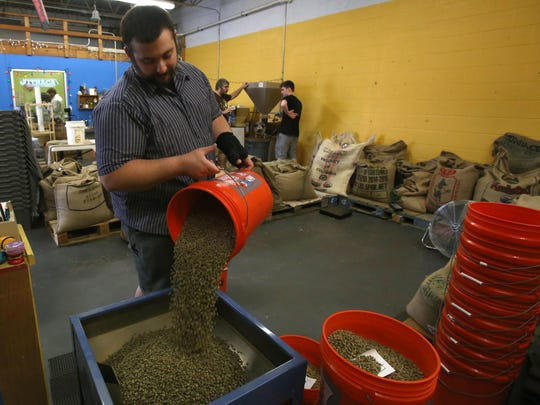Chris Ganger, the head roaster, pours fresh coffee beans into the machine to roast. A roast takes less than 15 minutes.