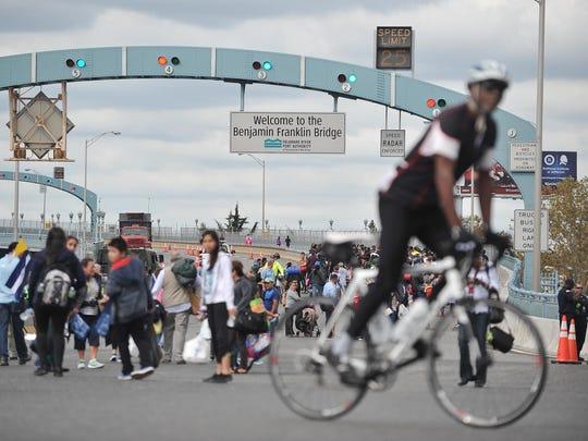 Pedestrians cross the Ben Franklin Bridge on Saturday afternoon.