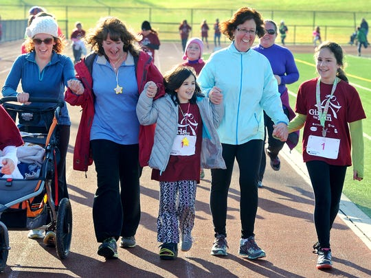 Irelyn Verno, center, walks the last leg of the Girls on the Run 5k with the help of, from left: mom, Devon; aunt, Nancy Speicher; grandmother, Tracy Carney and sister, Novalea at Central York High School on Saturday, Dec. 5, 2015. The 9-year-old girl suffers from Osteogenesis Imperfecta, or Brittle Bone Disease and spent most of the race in a racing stroller, pushed by family members. Over her short lifespan, Irelyn has had over fifty bone breaks and surgeries, but did not let that prevent her from completing her second Girl on the Run race.
