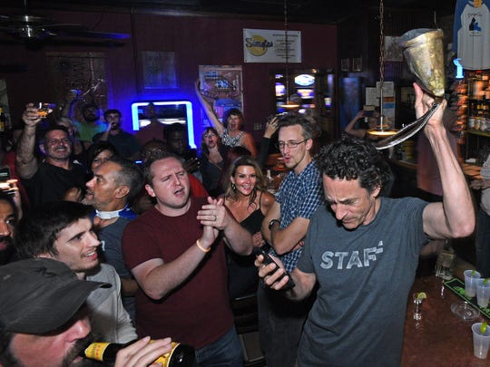 Gregory Kallenberg rings a cow bell at midnight at