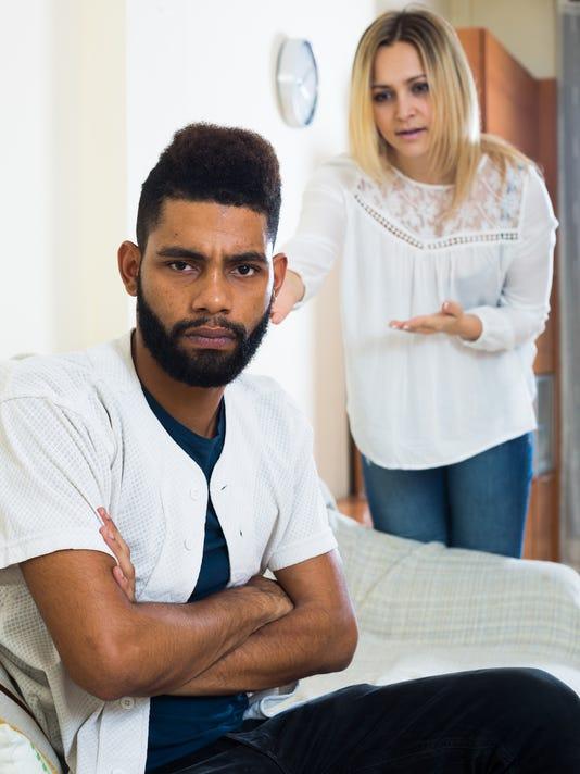 Blonde girl yelling at black boyfriend as quarreling indoors