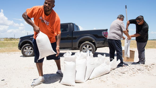 Anthony Rayford loads sandbags behind the Seaman's Memorial Tower in Aransas Pass ahead of tropical depression Harvey on Wednesday, Aug. 23, 2017.